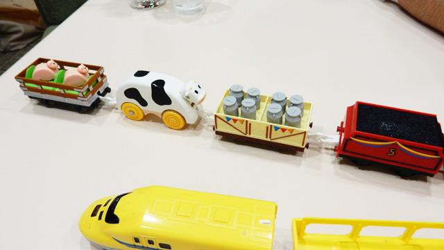 牛が、ミルクや豚の乗った貨物を運ぶ。多分出荷のために。プラレールってこんなことになっていたのか。