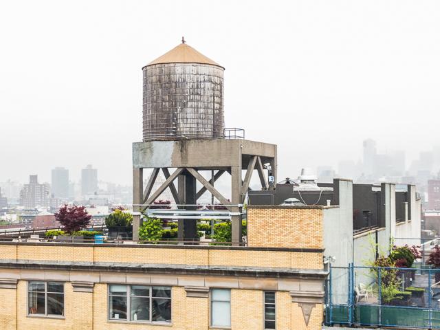 けぶるマンハッタンに、台にのってすっくとたつ給水タンク。