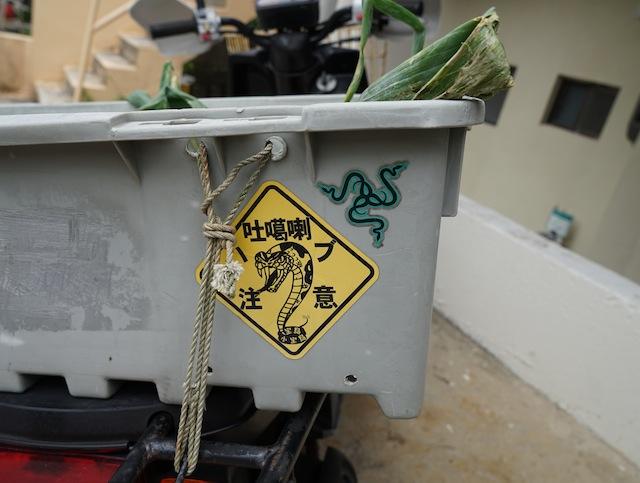 目指すはこのヘビ。島の売店で売っているハブ注意ステッカー。