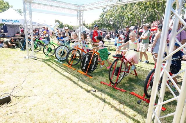 子供が自転車をこいで発電した電気で大人がライブをやっている