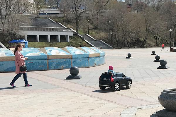 すごく小さな子供が妙にリアルな車に乗ってる(大人がラジコンで操作してる)