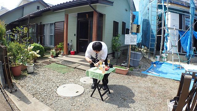 実家の玄関先でポテトサラダをリッツに乗せる江ノ島くん。