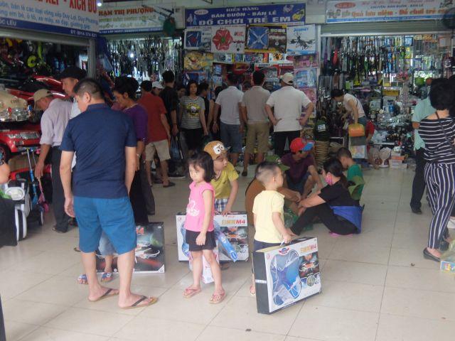 市場で中国製ドローンおもちゃを買う子供たち