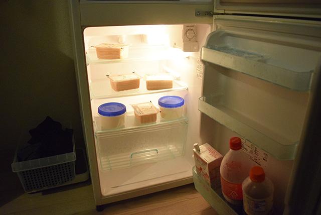 奥に豆腐と丸いタッパー。 手前には豆乳と麺つゆとコーラがあるというシンプルな内容。