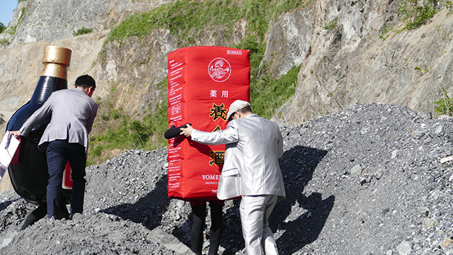 タキシードに腕を引かれて採石場の砂利山を下りる養命酒の新パッケージ。要素が多すぎて意味が分からない。