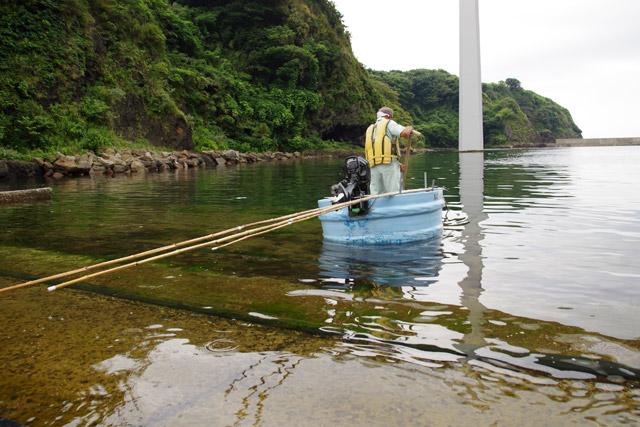 昔ながらの櫂を漕いで出船。たらい舟は前側に立って操船するのが特徴だ。