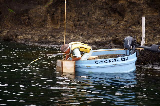 海底のサザエを見つけると、水深に合わせたサザエヤスを手に取って、水中にスルスルと落とし込む。