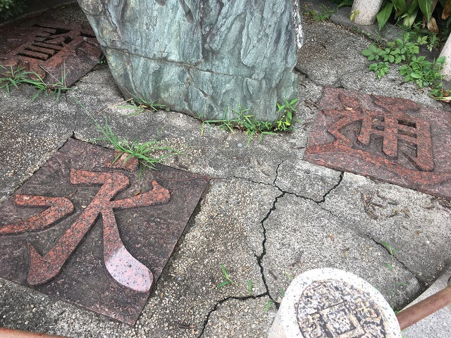 石碑を囲む「寛永通宝」の文字