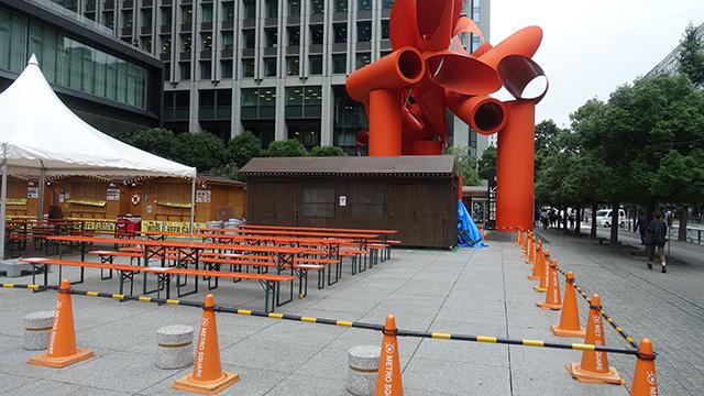 公共彫刻は周りの環境に左右される。只今ビアガーデン開催中。ベンチと机の色は作品に合わせているのではないか。となると、彫刻作品が環境に作用を及ぼしていることになる