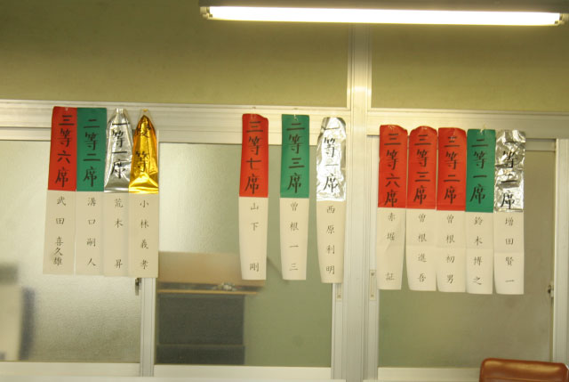 ちなみにマイク近くの壁には品評会の入賞者が賞ごとに掲示されている。運動会の順位別カラーのようでワクワクする