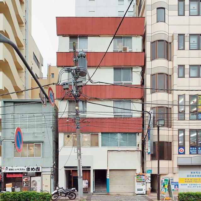 画面を左右に横切る電線と、手前にぐいんと伸びてる電線に加え、対象のビルに引き込まれる線。そして電柱の上のトランス。テーパーがかかった茶褐色の腰壁ビルに花を添えていると思う。