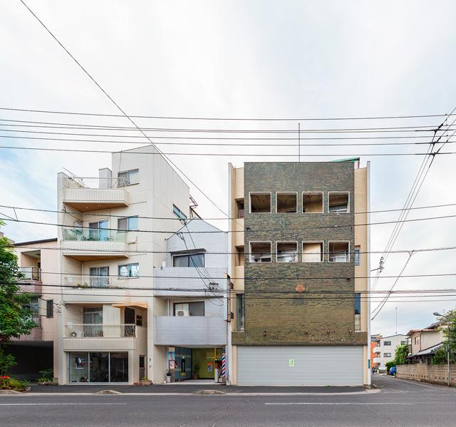 見ると、同じブロックに並んでいる建物は、みなベランダとビル本体が斜めになっている。
