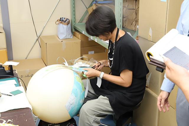 球体に貼り付けるためシートを切っていく職人、斎藤さん。