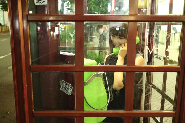 電話ボックスで笑っている女の子は想像をかき立てられる