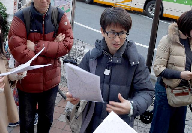 祝うべく集まった30名の友人一同。高田馬場駅前に集合。設計者として描画の説明を行うわたくし。真剣である。(実施されたのは半年前の冬のさなかでのこと。みんな厚着なのはそのためです)。