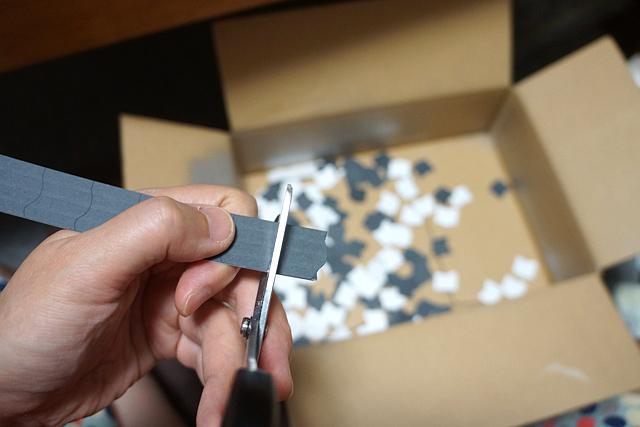 適当に形を作って増殖させて厚紙にプリントした瓦を、一枚一枚切り離す。来年こそレーザーカッターとかその類の便利なものを揃えよう…。