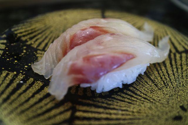 豪華な色の皿にのる寿司になったハタ