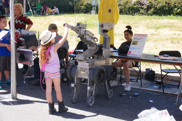 There were children calmly touching mysteriously tough-looking robot.