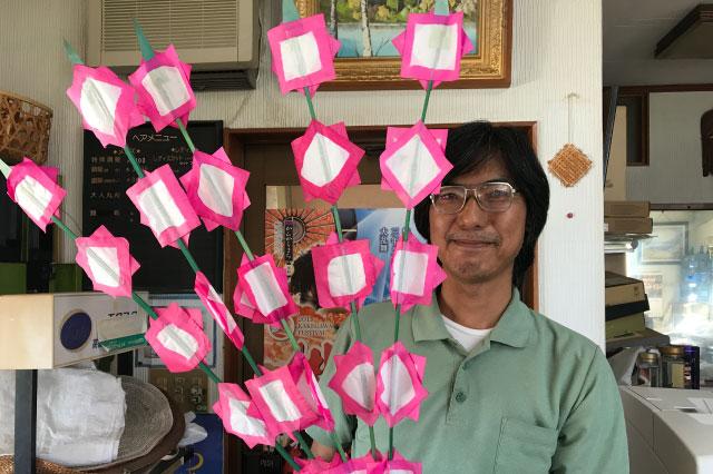 深田さんとピンクの花。本来は持って写真を撮るものではないが、無理やり持ってもらった