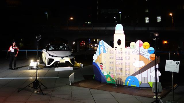 カオハメザワールドの電源はトヨタの車から供給。左はオープニングイベントで挨拶する高橋さん。