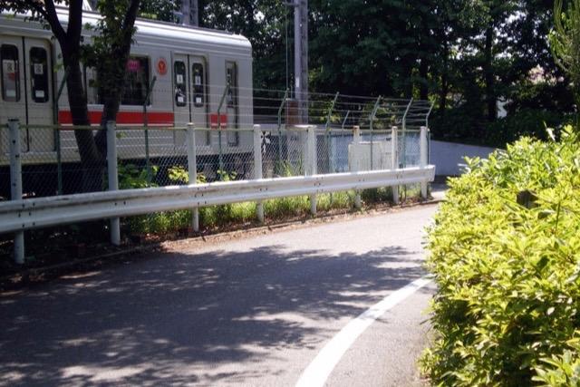 ふつうの道路のすぐ脇に電車が停まっている風景