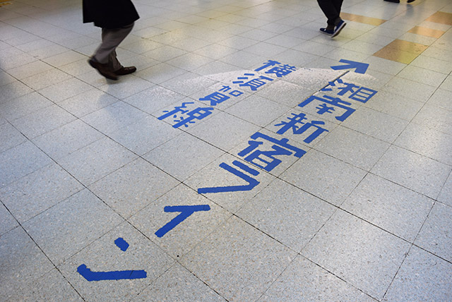 テープを貼って作った案内表示が通行人の足によって少しずつ削れて生まれた丸っこさが良い。