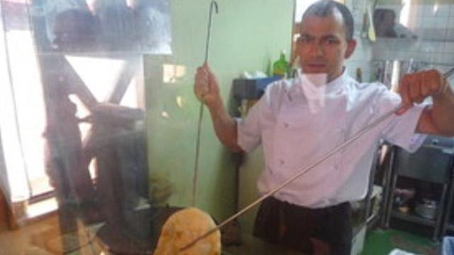 モハンさん。タンドール釜でナンを焼く写真