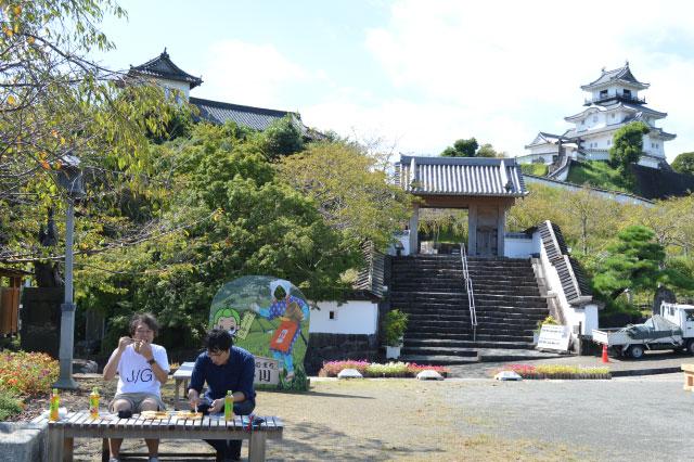 昼間の掛川城を背にどんどんのから揚げ弁当を食べる編集部・林さんとライター・西村さん(「静岡のローカルチェーン「お弁当どんどん」のから揚げ弁当はご飯が食べたくなる」 より)