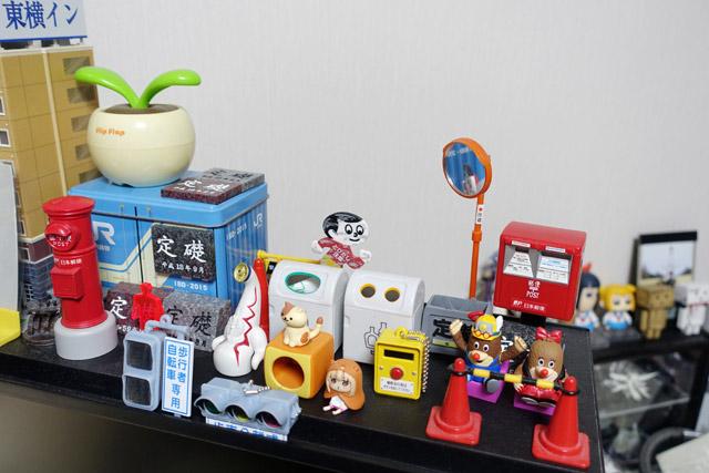 私の机の上にもたくさんのガチャが。ここは一軍の置き場なので、日々新しいのに入れ替わっている。特に信号機と押しボタンはお気に入り