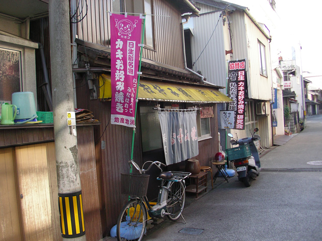 映画のセットみたいなお好み焼き屋。店の前に止まっている自転車が電動アシスト付きなのが現代風。