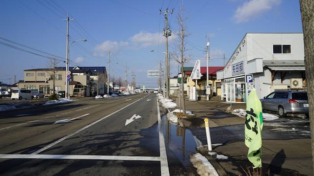 駅前から国道7号線につながる通り。理容店や精肉店などが点在する。