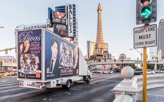おもしろいのは、車向けに道路に直角に立つ看板の中を、歩行者向けの広告を背負った車が行き交うという光景。