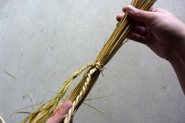 続いて、作った縄で稲藁の束を結ぶ。
