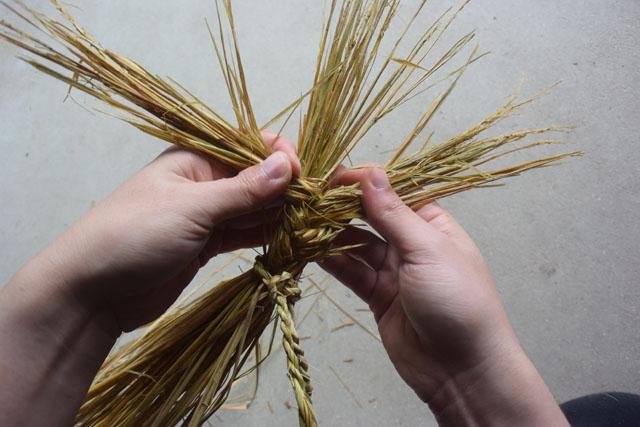 稲藁の束を髪の毛の三つ編みと同じ要領で編んでいく。
