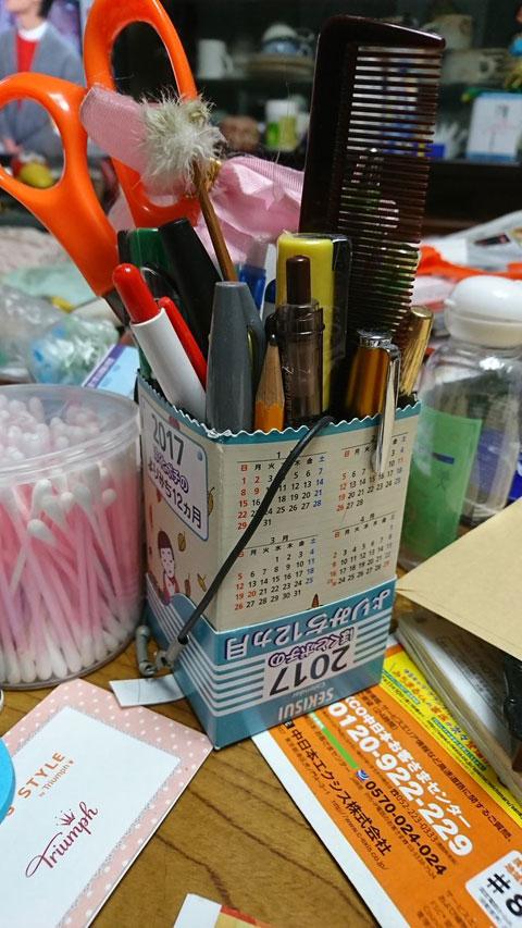 片付け途中の乱雑な居間の机よりペンが立ってるのはロール式カレンダーの空き箱だし入ってるものも統一感ないし (エビリズム)