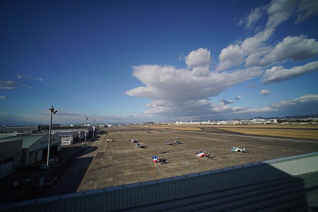 すぐそこで小型機やヘリコプターがまさに整備を受けているのが見える。壁の向こうは本物の飛行場。