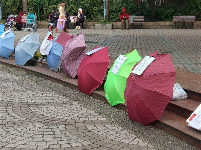 このひしめき合う傘と、その上の貼り紙は…!?