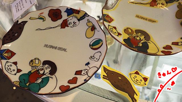 こちらはワークショップ用のお皿。シールをお皿に貼って転写させ焼き付ける事で、左側のお皿のようになる。