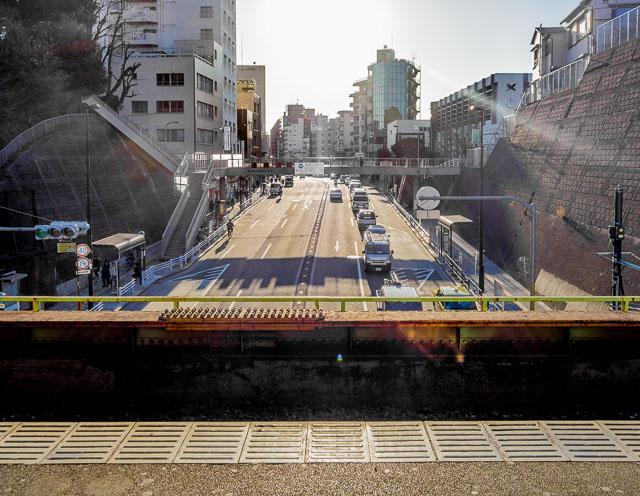 本稿執筆現在暫定日本一の道の上の駅・西日暮里駅。そのホームからの眺め。向こうから道路がやってきて、足元の下をくぐっていく。とてもいい。
