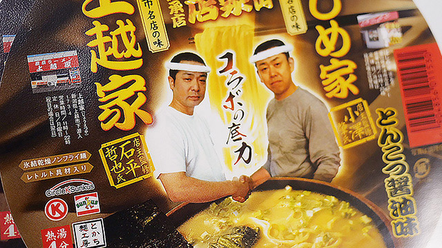 ラーメンの淵に存在し、手がスープにつかろうとするコラボ