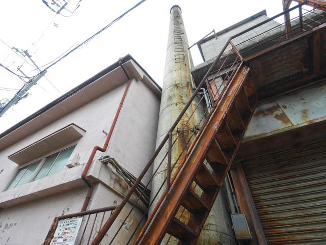 真下から見上げると、はるか上方に伸びる煙突。足場が付いてるものの、高所恐怖症気味の自分にはとても上れない。思い出すのは、飯村昭彦さんの麻布谷町「無用煙突」の写真である(『超芸術トマソン』の表紙写真)