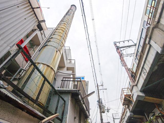 すぐ横にはJRの高架線。煙突と電車を同時に見上げることができる