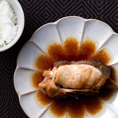 例の煮汁で仕上げたカマの煮つけ。煮汁に浮く尋常でない量の油を見よ。甘辛の味付けでご飯が進む進む。