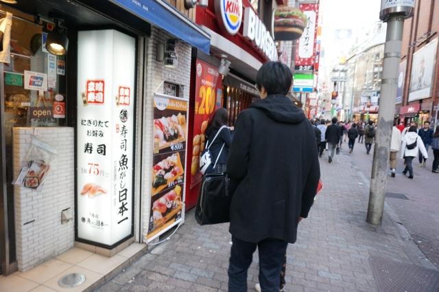 寿司屋のメニュー垂れ幕の前でおもむろに立ち止まる。