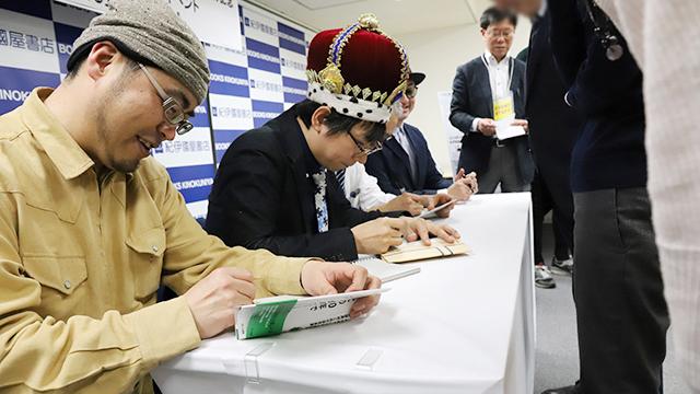 人生初のサイン会で、人生初のサインを書いてます。