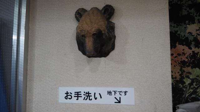 木彫りの熊の顔が壁に張り付いている。