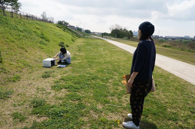古賀さんが電子レンジを河原に置いた、のを遠くから見つめる。