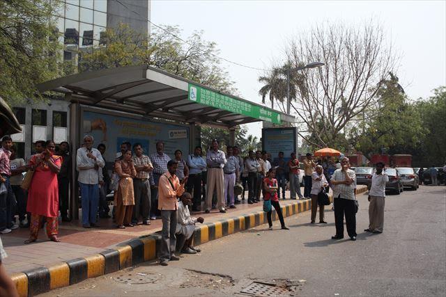 インド写真4、『たくさんの人がバスを待っている様子を撮りたくて道に出たんですが、全員がこちらを向いたためカメラ目線が凝縮された写真になりました』