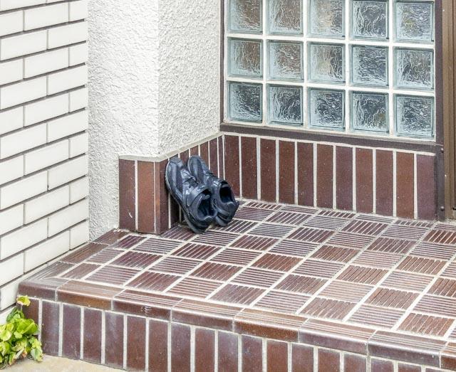 ブラウンにホワイト、そしてガラスブロックという落ち着いた玄関に黒いスニーカー。シック。