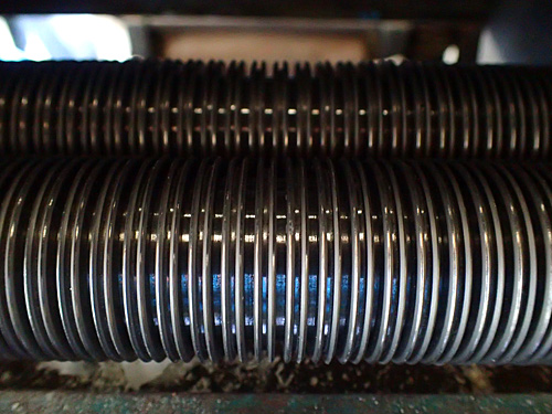 伸ばされた生地は、チャンポン用の切刃(丸麺用)で細長くカットされる。